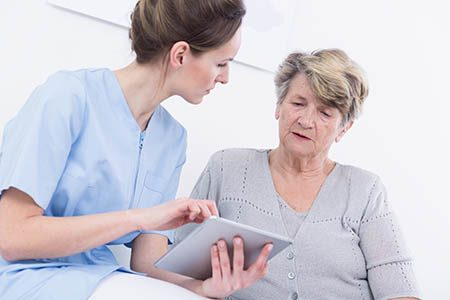 holding a tablet and talking to her patient