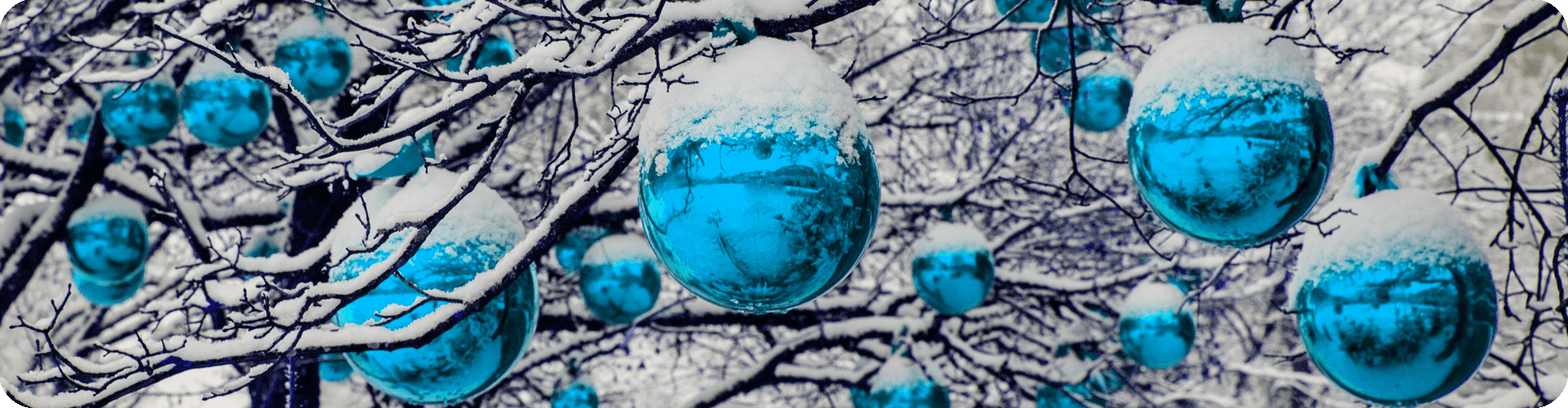 blue snowy christmas baubles hanging from trees