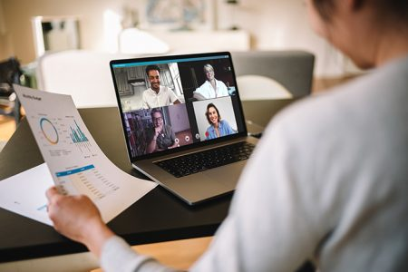 Woman holding a business report working at home having a video conference with colleagues. Over the shoulder view of a businesswoman having online business meeting from home.
